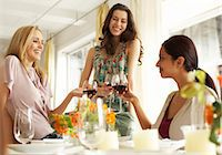 Three women raising glasses of red wine at dinner party, smiling Stock Photo - Premium Royalty-Freenull, Code: 6106-06978993