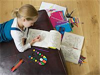 Girl (5-7) colouring in book, elevated view Stock Photo - Premium Royalty-Freenull, Code: 6106-06979051