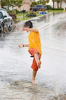 preteen swimsuit - Boy (10-12) playing in puddle of water in rain Stock Photo - Premium Royalty-Freenull, Code: 6106-06979055