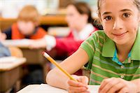 education concept - Children (8-10) in classroom (focus on girl writing in foreground) Stock Photo - Premium Royalty-Freenull, Code: 6106-06979122