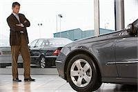 Businessman standing in front of car in showroom with arms folded Stock Photo - Premium Royalty-Freenull, Code: 6106-06979290