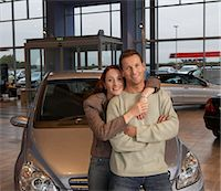 Couple in car showroom, woman with arms around man, smiling, portrait Stock Photo - Premium Royalty-Freenull, Code: 6106-06979293