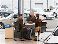 Mature salesman sitting at desk with couple in car showroom Stock Photo - Premium Royalty-Freenull, Code: 6106-06979294