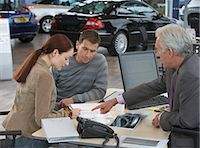 Couple sitting at desk signing document, mature car salesman pointing Stock Photo - Premium Royalty-Freenull, Code: 6106-06979295