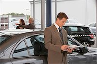 Man leaning against car in showroom, woman and salesman in background Stock Photo - Premium Royalty-Freenull, Code: 6106-06979296