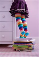pantyhose kid - Girl (3-5) standing on tip toes on pile of books, low section Stock Photo - Premium Royalty-Freenull, Code: 6106-06979481