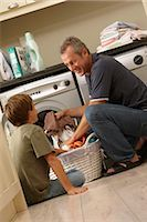 Boy (9-11) helping father load washing machine Stock Photo - Premium Royalty-Freenull, Code: 6106-06979507