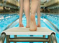 Girl (10-12) preparing to jump of diving board, low section Stock Photo - Premium Royalty-Freenull, Code: 6106-06979908