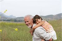 Grandfather giving girl (4-6) piggyback, smiling, portrait, side view Stock Photo - Premium Royalty-Freenull, Code: 6106-06980153
