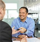 Man sitting at desk in car showroom taking key from salesman, smiling Stock Photo - Premium Royalty-Freenull, Code: 6106-06980211