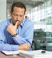 Man sitting in car showroom resting elbow on desk, looking downwards Stock Photo - Premium Royalty-Freenull, Code: 6106-06980213