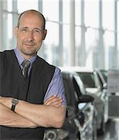 Car salesman in showroom, arms folded, smiling, portrait Stock Photo - Premium Royalty-Freenull, Code: 6106-06980215
