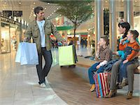 shopping mall - Father carrying shopping bags walking towards family, smiling Stock Photo - Premium Royalty-Freenull, Code: 6106-06980385
