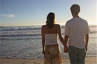 Teenage boy (14-16) and young woman holding hands on beach, rear view Stock Photo - Premium Royalty-Freenull, Code: 6106-06980695