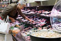 Mature woman looking at meat in supermarket, side view, close-up Stock Photo - Premium Royalty-Freenull, Code: 6106-06980728