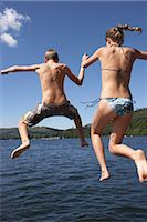 Teenage boy and girl (12-14) jumping into lake, rear view Stock Photo - Premium Royalty-Freenull, Code: 6106-06980840