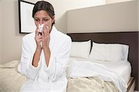 people coughing or sneezing - Young woman in bathrobe sitting on edge of bed, blowing nose Stock Photo - Premium Royalty-Freenull, Code: 6106-06981074