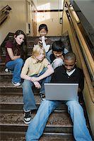 Group of students (9-13) using laptop on stairway in school corridor Stock Photo - Premium Royalty-Freenull, Code: 6106-06981092