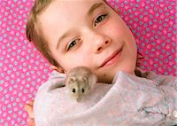 Girl (7-9) holding pet hamster, smiling, portrait, close-up Stock Photo - Premium Royalty-Freenull, Code: 6106-06981689