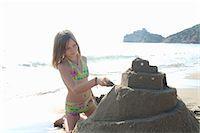 Girl (10-12) building sandcastle on beach Stock Photo - Premium Royalty-Freenull, Code: 6106-06981696