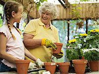 Young girl (10-11) potting flowers with grandmother in glasshouse, smiling Stock Photo - Premium Royalty-Freenull, Code: 6106-06982720