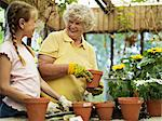 Young girl (10-11) potting flowers with grandmother in glasshouse, smiling