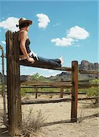 Cowgirl sitting on ranch fence Stock Photo - Premium Royalty-Freenull, Code: 6106-06982752