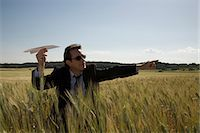 Businessman aiming paper plane in wheat field Stock Photo - Premium Royalty-Freenull, Code: 6106-06982898