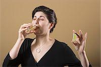 Woman drinking tequila, holding lemon slice Stock Photo - Premium Royalty-Freenull, Code: 6106-06983140