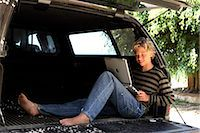 Teenage boy (14-15) sitting in back of truck, using laptop, smiling Stock Photo - Premium Royalty-Freenull, Code: 6106-06983177