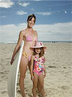 Mother and daughter (6-7) with surfboard on beach, portrait Stock Photo - Premium Royalty-Freenull, Code: 6106-06983299
