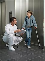 Doctor squatting by girl (7-10) on crutches Stock Photo - Premium Royalty-Freenull, Code: 6106-06983383