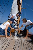 sports and sailing - Sailboat crew on deck winding capstan, low angle view Stock Photo - Premium Royalty-Freenull, Code: 6106-06984074