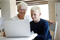 Grandmother and grandson (12-13) using laptop together Stock Photo - Premium Royalty-Freenull, Code: 6106-06984233