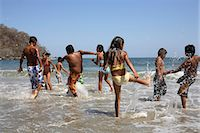 preteen girl wet clothes - Children (5-10) playing and splashing in sea Stock Photo - Premium Royalty-Freenull, Code: 6106-06984644