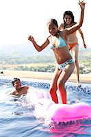 Teenagers (15-19) jumping in swimming pool Stock Photo - Premium Royalty-Freenull, Code: 6106-06984719