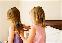 Two sisters (5-8),one brushing sisters hair on bed Stock Photo - Premium Royalty-Freenull, Code: 6106-06984928