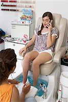 Young woman receiving pedicure while using mobile phone Stock Photo - Premium Royalty-Freenull, Code: 6106-06985209