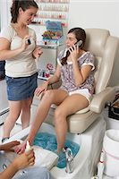 Young woman receiving pedicure while using mobile phone, woman showing nail polish Stock Photo - Premium Royalty-Freenull, Code: 6106-06985210