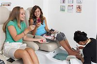 Young woman receiving pedicure, friend looking at mobile phone, smiling Stock Photo - Premium Royalty-Freenull, Code: 6106-06985212