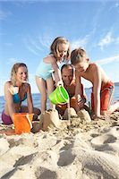 Family with daughter (7-9) and son (11-13) building sandcastles on beach Stock Photo - Premium Royalty-Freenull, Code: 6106-06985409