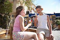 Girl (7-9) and boy (11-13) eating ice cream on fountain Stock Photo - Premium Royalty-Freenull, Code: 6106-06985433