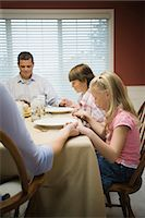 Parents with children (8-13) praying at table, heads bowed, holding hands Stock Photo - Premium Royalty-Freenull, Code: 6106-06985610