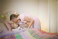 daughter kissing mother - Mother kissing daughter (8-9) goodnight in bed Stock Photo - Premium Royalty-Freenull, Code: 6106-06985632