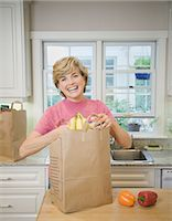 Senior woman with grocery bag in kitchen, smiling, portrait Stock Photo - Premium Royalty-Freenull, Code: 6106-06986360