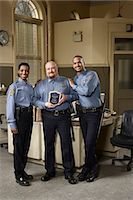 female police officer happy - Three police officers, one holding award, portrait Stock Photo - Premium Royalty-Freenull, Code: 6106-06986804