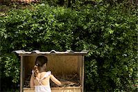 Girl (6-7) standing by rabbit hutch, rear view Stock Photo - Premium Royalty-Freenull, Code: 6106-06987291