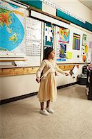 story - Girl (8-9) standing and gesturing in front of classroom, side view Stock Photo - Premium Royalty-Freenull, Code: 6106-06987374