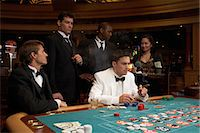 Four men sitting in casino playing roulette, one smoking cigar, waitress serving drinks Stock Photo - Premium Royalty-Freenull, Code: 6106-06988142