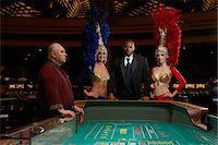 Portrait of man posing at roulette table with two dancers and senior casino worker Stock Photo - Premium Royalty-Freenull, Code: 6106-06988147